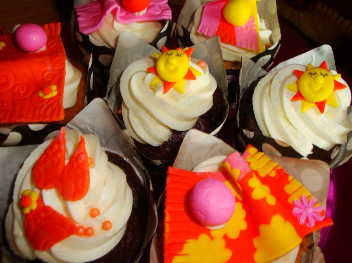 Cupcakes with suns, bikinis, towels & beach balls